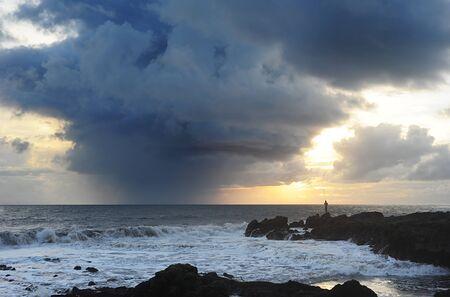 Fisherman fishing at sunset before storm photo