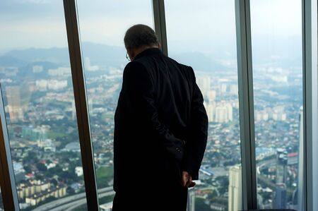 Kuala Lumpur, Malaysia - April 4, 2011: Businessman looking through the window of Petronas Twin Tower down to Kuala Lumpur city. Petronas Twin Towers  are skyscrapers and  the tallest twin buildings in the world. Stock Photo - 9716328