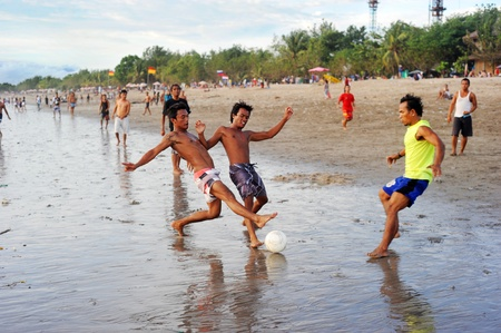 Bali, Indonesia - April 4, 2011: People plaing soccer on the  Kuta beach.Kutas six-kilometer-long, crescent-shaped surfing beach, protected by a coral reef at its southern end, and long and wide enough for Frisbee contests and soccer games, is famous for