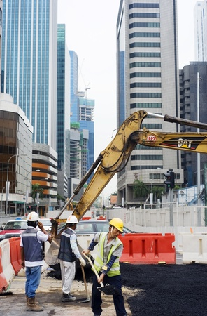 Singapore, Republic of Singapore - May 02, 2011: Workers repairing roads on the one of Singapore city street