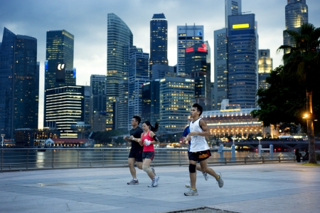 sea life centre: Singapore, Republic of Singapore - May 3, 2011: People running in the evening on embankment in front of business center. Running is very popular sports in Singapore