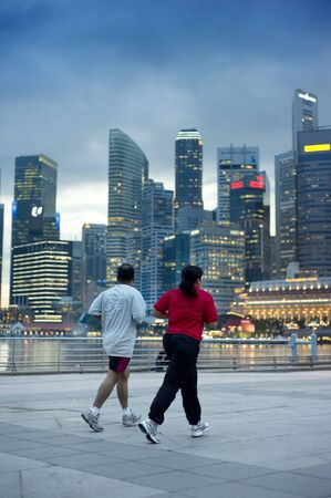 Singapore, Republic of Singapore - May 3, 2011: People running in the evening on embankment in front of business center. Running is very popular sports in Singapore Stock Photo - 9716332
