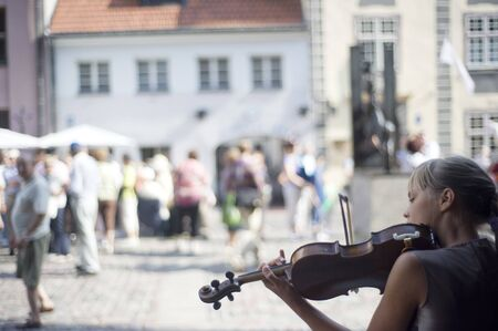 latvia girls: RIGA, LATVIA - AUGUST 9, 2010: Young girl playing violin on the street of Riga Editorial