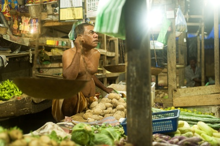 Galle, Sri Lanka - January 28, 2011: Seller at a street market. Street market is the component of traditional Sri Lankan culture.