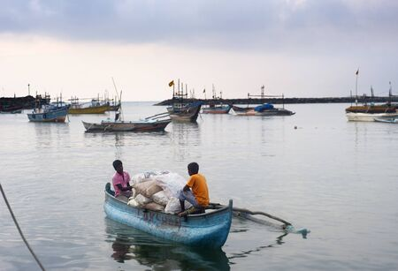 Ambalangoda, Sri Lanka - January 28, 2011:Harbour with fishermans boat at sunset. Fishing in Sri Lanka is a tough job but this is the way they earn their living Stock Photo - 9768079