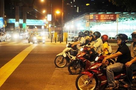 Kuala Lumpur, Malaysia - March 03, 2011: Motorcyclists stading on junction in Kuala Lumpur in the evening.