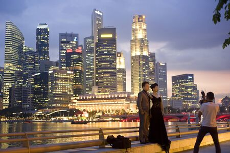 Singapore, Republic of Singapore - May 3, 2011: Photographer take a picture of just a married couple  in front of Singapore business centre - famous place in Singapore