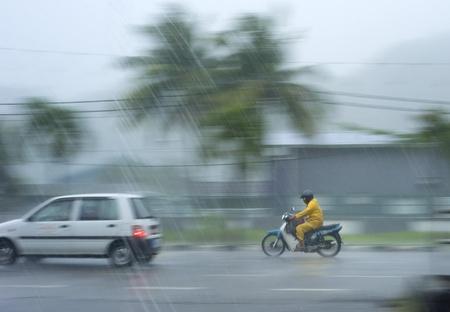 motociclista: Kedah, Malasia - 28 de marzo de 2011: Tráfico de las fuertes lluvias en Malasia