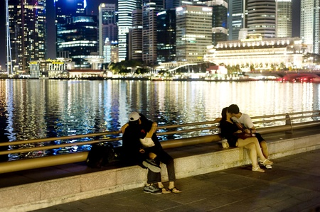 Singapore, Republic of Singapore - May 02, 2011: Teenage couples kissing on embankment of Singapore
