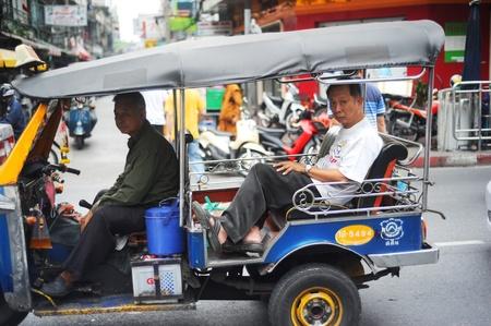 Bangkok, Thailand  -  March 26, 2011: Bangkok Tuk-tuk with passengers in traffic jam