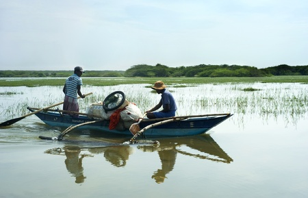 pescador: Bentota, Sri Lanka - 13, 2001: Dos hombres de Sri Lanka que flotan en el barco por el r�o peque�o.