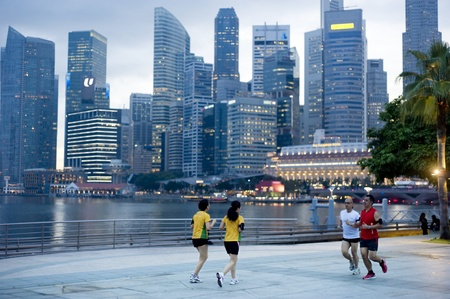 Singapore, Republic of Singapore - May 3, 2011: People running in the evening on embankment in front of business center. Running is very popular sports in Singapore
