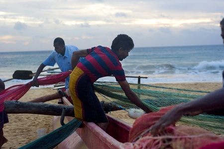 Hikkaduwa, Sri Lanka - February 21, 2011: Group of Sri Lankan fishermen packing fishing net. Fishing in Sri Lanka is a tough job but this is the way they earn their living