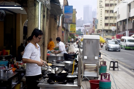 Kuala Lumpur, Malaysia - March 17, 2011: Local man cooking fast food on the street in Kuala Lumpurs Chinatown. KL Chinatown is a popular tourist attraction and a food haven