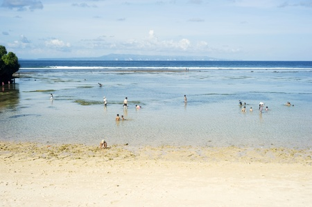enclave: Nusa dua, Bali, Indonesia - April 17, 2011: People swimming in the ocean during tide ebb. Nusa Dua is known as an enclave of large international 5-star resorts in south-eastern Bali.