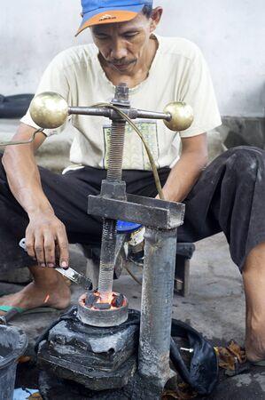 Probolingo, Indonesia - April 22, 2011: Unedentified  Indonesian man repair motorcycle inner tube Stock Photo - 10938533