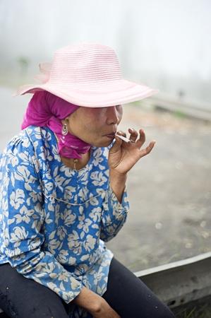 indonesian woman: Probolingo, Indonesia - Abril 24,2011: mujer no identificada indonesio tabaquismo. Consumo de tabaco en Indonesia es una pr�ctica com�n, ya que m�s de 165 millones de personas fuman en Indonesia. Del pueblo de Indonesia, el 63% de los hombres y el 5% de las mujeres como los fumadores, un tota Editorial