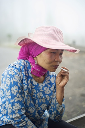 indian village: Probolingo, Indonesia - April 24,2011: Unidentified indonesian woman smoking  cigarette. Smoking in Indonesia is a common practice, as over 165 million people smoke in Indonesia. Of Indonesian people, 63% of men and 5% of women reported as smokers, a tota Editorial