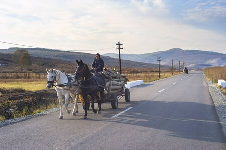 Hateg, Romania - October 25, 2011: Man driving horse cart by the country road. Horse cart on Romanian roads are a kind of landmark. Editorial