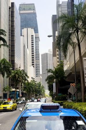 Taxi in the central sreet in Singapore. Sharpness on a blue car photo