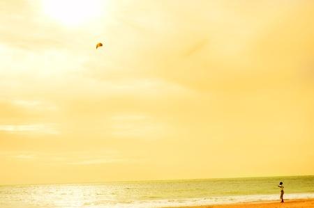 Boy playing wtih flying kite on the ocean beach. Sri Lanka photo