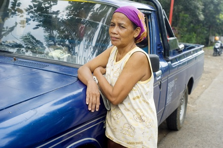 adult indonesia: Surabaya, Indoneia - April 22, 2011: Portrait of  indonesian woman near a car