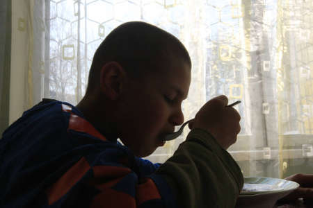 childrens food: Kiev, Ukraine - February 21, 2008: Boy at Shelter for Minors. Of Ukraine's nine million children some 65,000 live in state-run children's institutions such as orphanages, boarding schools and shelters.