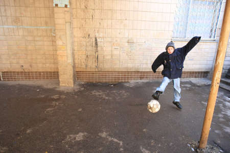 futbol infantil: Kiev, Ucrania - 21 de febrero de 2008: chico no identificado jugando con una pelota en el Albergue de Menores. De nueve millones de ni�os ucranianos unos 65.000 viven en instituciones estatales para ni�os, tales como orfanatos, internados y albergues.