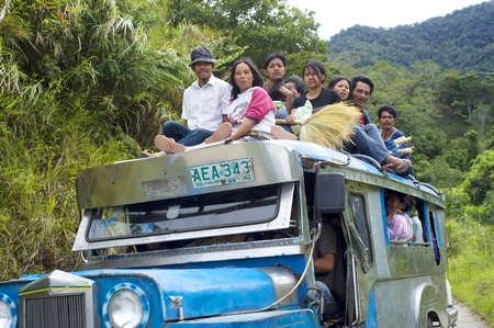 Bontoc, Philippines - March 26, 2012:  Passengers sit atop a very full jeepney The jeepney found everywhere in the country. It carries between 16 to 30 passengers. Stock Photo - 13455844