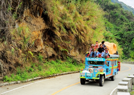 atop: Bontoc, Philippines - March 26, 2012:  Passengers sit atop a very full jeepney The jeepney found everywhere in the country. It carries between 16 to 30 passengers. Editorial