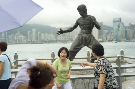 Hong Kong - May 19, 2012: Tourists taking picture at Statue of Bruce Lee at Avenue of Stars in Hong Kong. Overall visitor arrivals to Hong Kong in 2010 totalled just over 36 million