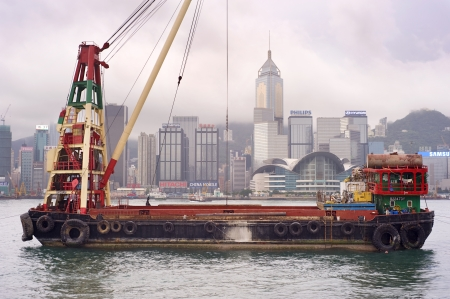 tonnes: Hong Kong S.A.R. - MAY 19, 2012: Barge in front of business district in Hong Kong.Some 456,000 vessels arrived in and departed from Hong Kong during the year, carrying 243 million tonnes of cargo