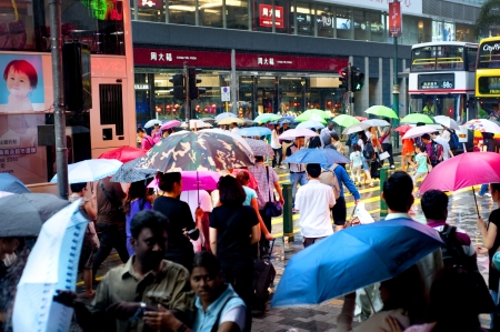 Hong Kong S.A.R. - MAY 20, 2012: People crossing the road in the rain.  With a land mass of 1,104 km and population of 7 million people, Hong Kong is one of the most densely populated areas in the world