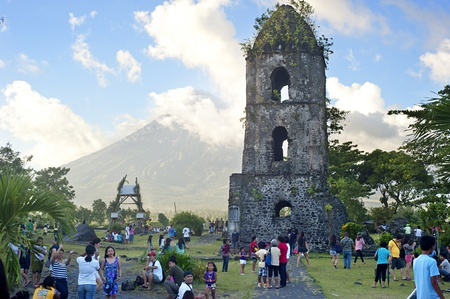 mayon: Legaspi, Philippines - April 08, 2012: Tourists at Cagsawa Ruins. The Cagsawa Ruins are the remnants of an 18th century Franciscan church,  built in 1724 and destroyed by the 1814 eruption of the Mayon Volcano
