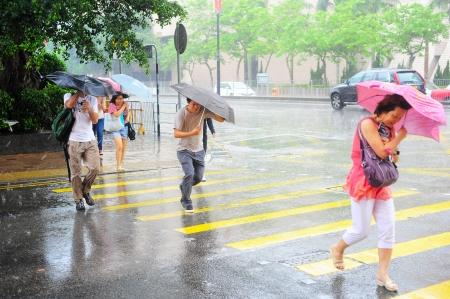 Hong Kong - 20 maggio 2012: Le persone che attraversano la strada sotto la pioggia. Con una massa di terra di 1104 km e una popolazione di 7 milioni di persone, Hong Kong è una delle aree più densamente popolate del mondo