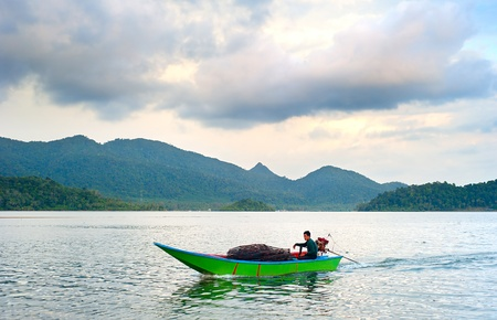 exporter: Ko Chang, Thailand - March 10, 2012: Fisherman returning to his home from fishing by motorized boat. Thailand is the world?s leading producer and exporter of shrimp products.  Editorial