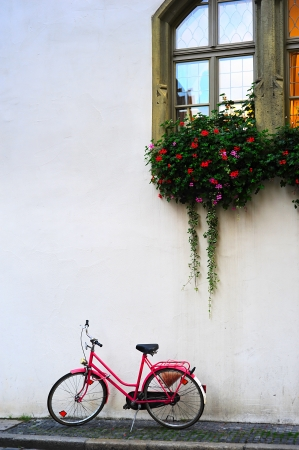 pink bike: Bicycle leaning against wall. Germany