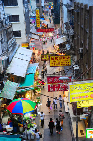 lightbox: Hong Kong - May 21, 2012: Aerial view on street market in Hong Kong. With a land mass of 1,104 km and population of 7 million people, Hong Kong is one of the most densely populated areas in the world