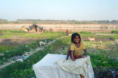 child poverty: Delhi, India - March 02, 2012: A portrait of a cute poor girl from India.  32.7% of the total Indian people fall below the international poverty line of US$ 1.25 per day while 68.7% live on less than US$ 2 per day. Editorial