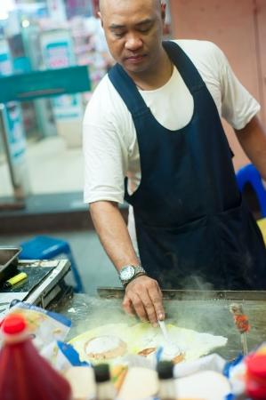 Kuala Lumpur, Malaysia - March 19, 2012: Local man cooks fast food on the street in Kuala Lumpur Stock Photo - 16943590