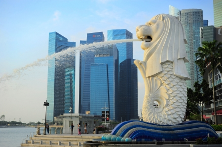 merlion: Singapore - March 08, 2013: The Merlion fountain spouts water in front of the Singapore skyline. Merlion is an imaginary creature with the head of a lion, often seen as a symbol of Singapore