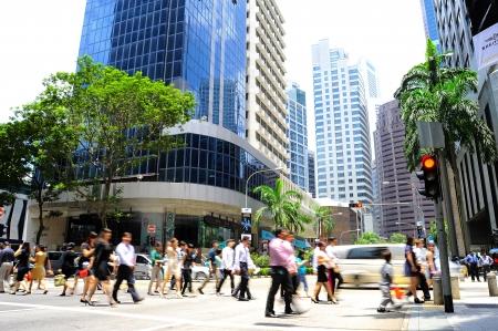 Singapore, Repubblica di Singapore - 7 mar 2013: gli uomini d'affari non identificati che attraversano la strada su 7 Marzo 2013 a Singapore. Ci sono più di 7.000 le imprese multinazionali provenienti da Stati Uniti, Giappone ed Europa a Singapore. Editoriali