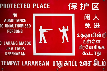Multilanguage warning sign at Singapore industrial site photo