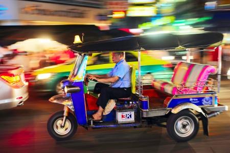 tuk tuk: Bangkok, Thailand - March 03, 2013: Tuk - tuk driver riding his tuk-tuk on Chinatown street at night .  There are more than 100,000 tuk-tuk in Bangkok.