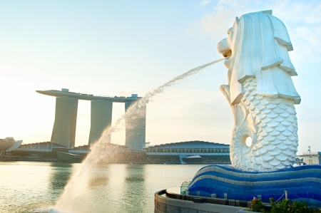 merlion: Singapore, Republic of Singapore - March 08, 2013: The Merlion fountain spouts water in front of the Marina Bay Sands hotel. Merlion is an imaginary creature with the head of a lion, often seen as a symbol of Singapore