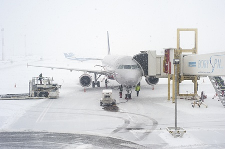 cold weather: Kiev, Ukraine - January 12, 2013: Unidentified workers prepairing an airplane duirng the snowfall. Kiev was covered by around 20 inches of snow, the largest amount to fall in one weekend since records in 1889 Editorial