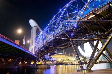 tonnes: Singapore, Republic of Singapore - March 06, 2013   The Helix Bridge and Marina Bay Sands at night   The Helix is fabricated from 650 tonnes of Duplex Stainless Steel and 1000 tonnes of carbon steel