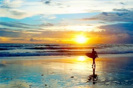 Surfer sulla spiaggia mare al tramonto sull'isola di Bali, Indonesia Archivio Fotografico