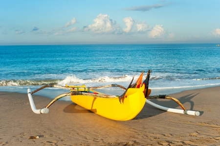 Traditional indonesian fishing boat on Bali ocean beach at sunset photo