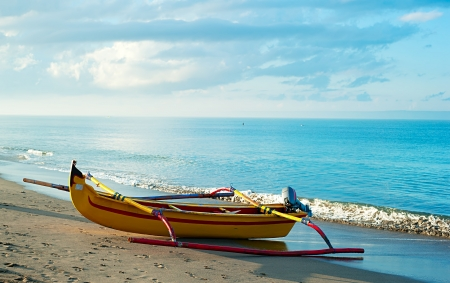 Traditional indonesian fishing boat on Bali ocean beach at sunrise photo